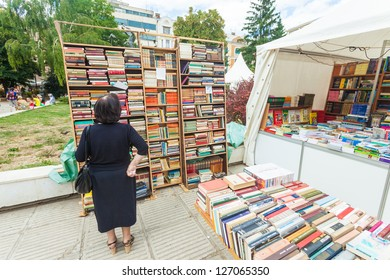 SARAJEVO, BOSNIA - AUGUST 11: Woman perusing bookshelves on street market on August 11, 2012 in Sarajevo, Bosnia. Outdoor book markets are common occurrence in the cultural city of Sarajevo.