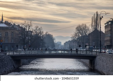 SARAJEVO, BOSNIA - FEBRUARY 17, 2018: Pedestrians passing by a bridge on the Miljacka river in Sarajevo at Sunset. Miljacka is one of the two rivers of the capital city of Bosnia