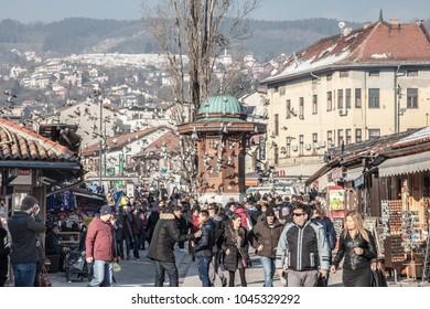 SARAJEVO, BOSNIA AND HERZEGOVINA - FEBRUARY 16, 2018: Pigeons flying over the Bascarsija square Sebilj fountain. Bascarsija is the symbol of Sarajevo, with its oriental architecture