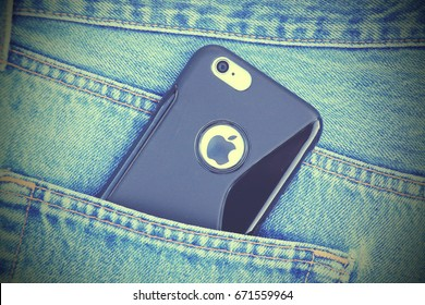 SARAJEVO , BOSNIA AND HERZEGOVINA - JUNE 03 , 2015: Retro old film style photo of silver iPhone 6 with black case in jeans pocket. iPhone 6 was created and developed by the Apple inc.
