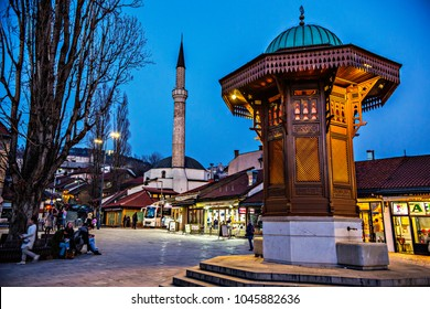 SARAJEVO, BOSNIA AND HERZEGOVINA - March 2018: Sebilj fountain in Pigeon Square, Bascarsija quarter by evening in lights, Sarajevo, Bosnia and Herzegovina