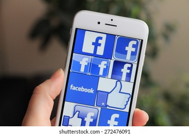 SARAJEVO , BOSNIA AND HERZEGOVINA - MARCH 28, 2015: Woman watch Facebook icons on Apple iPhone 6. Facebook is largest and most popular social networking site in the world.