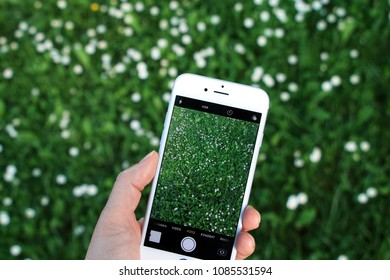 SARAJEVO - BOSNIA AND HERZEGOVINA - MAY 07 , 2018 : Woman holding new iphone and taking photo in green grass.