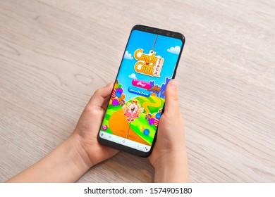 Sarajevo, Bosnia and Herzegovina - November 30, 2019: Boy holding Samsung Galaxy S9 plus phone with Candy Crush Saga puzzle video game close-up