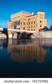 SARAJEVO, BOSNIA AND HERZEGOVINA - October 21, 2017 - The renovated building of Sarajevo City Hall is lit by early morning sunlight and reflected in Miljacka River