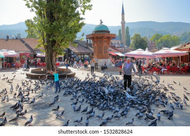 SARAJEVO, BOSNIA AND HERZEGOVINA - SEPTEMBER 15, 2019: A local man feeding pigeons in front of the wooden fountain Sebilj, with Bascarsija Mosque in the background