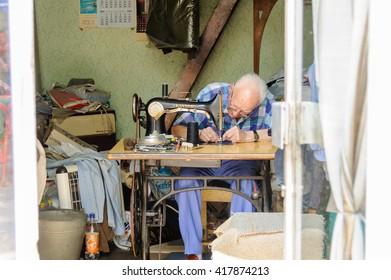 SARAJEVO, BOSNIA AND HERZEGOVINA - SEPTEMBER 4, 2009: Elderly man working on an old treadle sewing machine