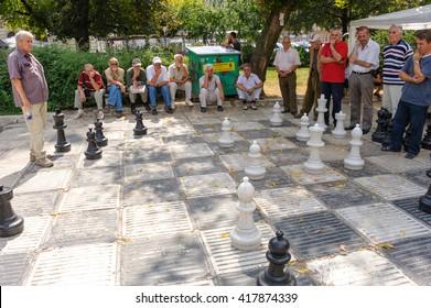SARAJEVO, BOSNIA AND HERZEGOVINA - SEPTEMBER 4, 2009: Senior men preoccupied with an outdoor giant chess game