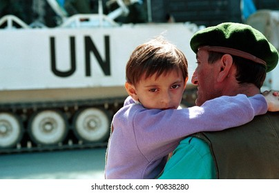 SARAJEVO, BOSNIA - JULY 19: A Bosnian boy and his father watch United Nations troop carriers drive through the besieged city on June 19, 1994 in Sarajevo, Bosnia.