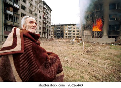 SARAJEVO, BOSNIA - MARCH 17: A Bosnian Croat man sits stunned and scared outside his burning home after rampaging Bosnian Serbs looted and set fire to his home in the final hours of siege on Mar 17, 1996 in Sarajevo, Bosnia.