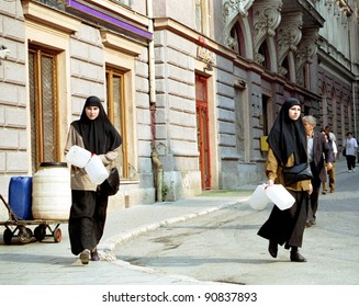 SARAJEVO, BOSNIA - OCTOBER 1: Girls in traditional Islamic dress walk towards a public water well in the center of the besieged Bosnian capital on Oct 1, 1994 in Sarajevo, Bosnia.
