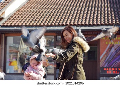 Sarajevo,Europe, 09.02.2018. Mother and daughter enjoying play and feeding pigeons on city square downtown. Birds flying around people and lending on hands.