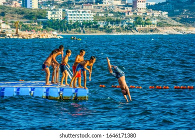 Sarande, Albania - August 04, 2014. Children jumping into the sea of the pier in summer