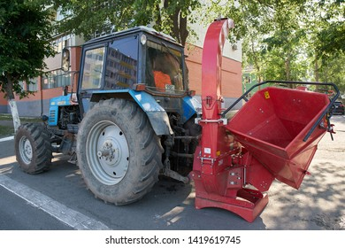 SARANSK, RUSSIA - JUNE 08, 2019: Tractor with attached wood chipper machine at city street.
