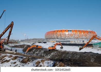 SARANSK, RUSSIA - MARCH 10, 2018: Excavator Cleaning Canal, Mordovia Arena stadium visible on the background.