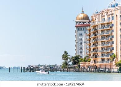 Sarasota, USA - April 28, 2018: Blue sky in Florida city during sunny day, bay, buildings for La Bellasara Condo Associates condominium complex, colorful domes, boat