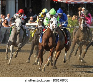 """SARATOGA SPRINGS - JUL 21: The field takes the club house turn in the Coaching Club American Oaks on Jul 21, 2012 in Saratoga Springs, NY. Eventual winner is """"Questing"""" (blue silks)."""