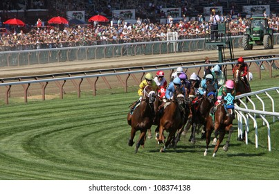 """SARATOGA SPRINGS - JUL 21: Horses take the club house turn in race 7 on Jul 21, 2012 at Saratoga Race Course in Saratoga Springs, NY. Eventual winner is Edgar Prado (pink cap) and """"Image of Disco""""."""