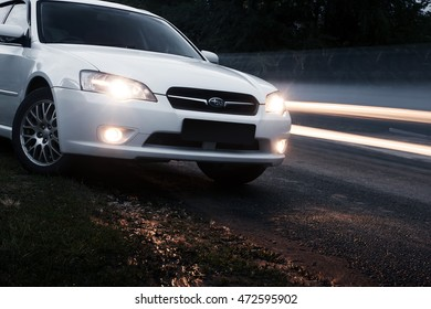 Saratov, Russia - August 28, 2014: Car Subaru Legacy stay on asphalt road near passing cars at dusk