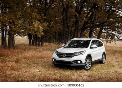 Saratov, Russia - August 29, 2014: White modern car Honda CRV stay on grass near forest at autumn