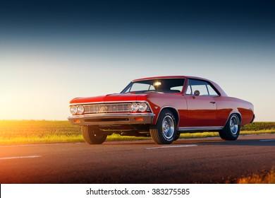 Saratov, Russia - June 07, 2015: Retro red car Chevrolet Malibu stay on asphalt road at sunset