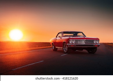 Saratov, Russia - June 07, 2015: Retro red car Chevrolet Malibu stay on asphalt road at sunset