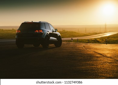 Saratov, Russia - June 07, 2018: Black car Volkswagen Touareg is parked at countryside asphalt road near highway at golden sunset