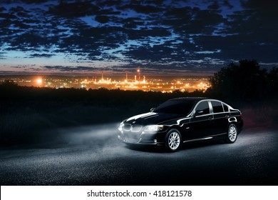 Saratov, Russia - June 12, 2015: Black car BMW E90 standing in the dark mist forest with views of the city at night