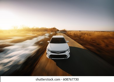Saratov, Russia - March 15, 2017: White car Toyota Camry XV50 is driven at empty countryside asphalt road at sunset
