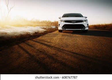 Saratov, Russia - March 15, 2017: White car Toyota Camry XV50 at empty countryside asphalt road at sunset