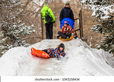 Saratov / Russia - March 8, 2018: Children ride with an ice slide. Winter vacation. Outdoor activity. Winter day in the city Park.