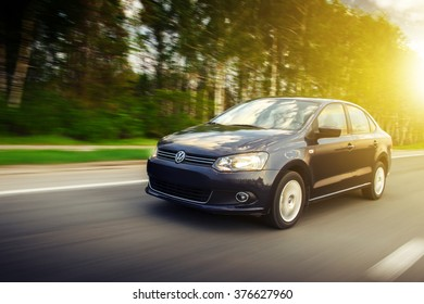Saratov, Russia - May 6, 2013: Blue car Volkswagen Polo Sedan fast speed drive on the asphalt road at sunset