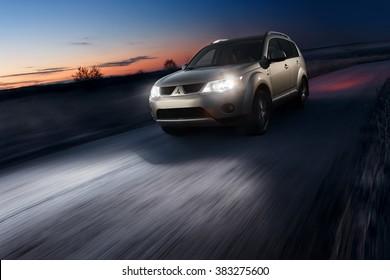 Saratov, Russia - November 27, 2014: Car Mitsubishi Outlander fast drive on asphalt road at dusk