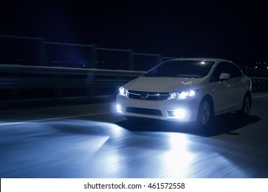 Saratov, Russia - October 23, 2012: White car Honda Civic with xenon headlights fast drive on road at night