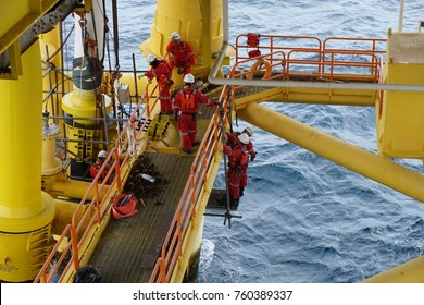 SARAWAK, MALAYSIA - February 22nd, 2017: Unidentified offshore scaffolders erecting the scaffolding at overboard complete wears personal protective equipment and helped by offshore workers on sea deck