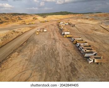 Sarawak, Malaysia – September 10, 2021:The :hoto showing an aerial view of heavy hauling and machinery equipment parking at construction site after finished earthwork site clearing.