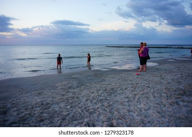 Sarbinowo, Poland - July 25, 2015: Mother and father watching their kids standing in the water at a beach in the evening with cloudy sky.