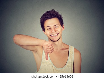 Sarcastic young man showing thumbs down sign hand gesture, happy someone made mistake, lost, failed isolated on gray background. Human emotion, facial expression, feeling attitude