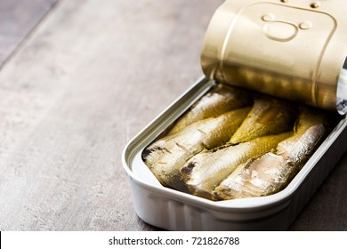Sardine cans of preserves on wooden table. Copyspace