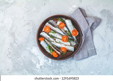 Sardines or baltic herring with parsley, tomatoes slices and spaces on ceramic plate on light gray concrete table surface. Raw uncooked sea fish, top view, copy space for you text, flat lay