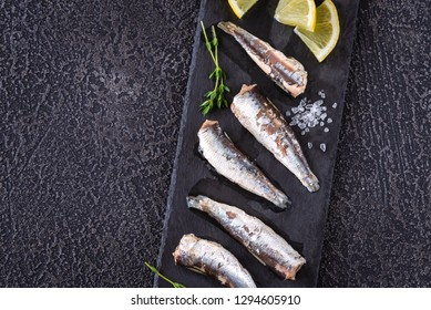 Sardines on the black stone board: top view