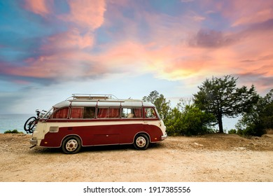 Sardinia, Italy, February 10, 2021. A Volkswagen T2 is parked on seafront promenade in Sardinia during a stunning sunset. The Volkswagen T2 it's known as the Transporter, Kombi or Microbus