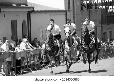 Sardinia, Italy. July 07, 2009. Three riders gallop parade through the streets of a village during a religious demonstration in front of dozens of spectators. Balck and white picture.