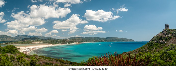Sardinia, Villasimius. Panoramic view of the Porto Giunco beach with turquoise sea water. On the promontory of Capo Carbonara, the famous Spanish sighting tower and the Notteri pond in the background