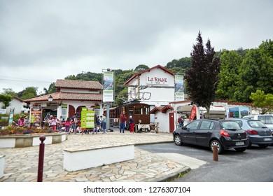 """Sare, France - June 21, 2018: The """"Petit Train de La Rhune'', typically Basque Col de Saint-Ignace train station, tourists near authentic cog railway, rolling stock, wooden carriages"""