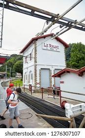 """Sare, France - June 21, 2018: The """"Petit Train de La Rhune'', typically Basque Col de Saint-Ignace train station, tourists near authentic cog railway"""