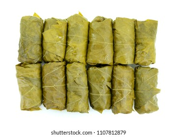 Sarma/dolmades/stuffed vine leaves with sliced lemon, isolated on white background