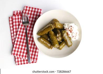 sarma/dolma/dolmadakia/stuffed vine leaves with yogurt on the side, red napkin, fork, white background, top view, sarmale