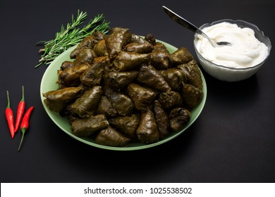 Sarmale, dolma, sarma, golubtsy or golabki. Grape vines leaves stuffed with meat, rice and vegetables with sour cream. European traditional cuisine. Fresh sarmale, Romanian and Moldovan typical food.