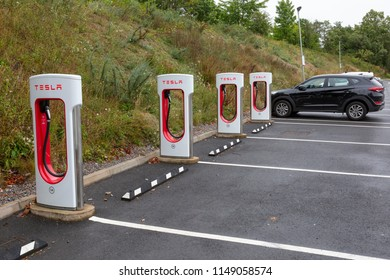 SARN, UNITED KINGDOM - AUGUST 2, 2018 : A row of Tesla Superchargers next to empty parking bays at the Sarn Park motorway services off the M4 near Bridgend in Wales.